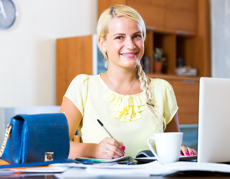 yuppie: Positive young woman working at laptop at home