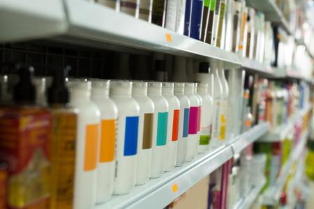 Planken met verschillende haarverzorgingsproducten in salon Stockfoto