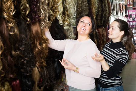 purchasers: Two smiling customers purchasing hair extension in salon Stock Photo