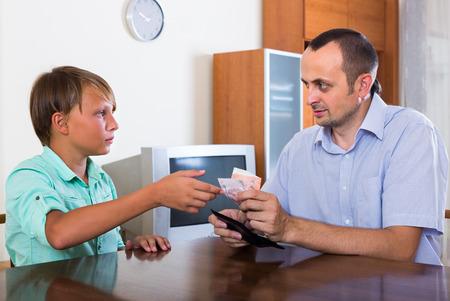 bolsa dinero: El muchacho del adolescente pidiendo padre por dinero pequeño bolsillo en el hogar