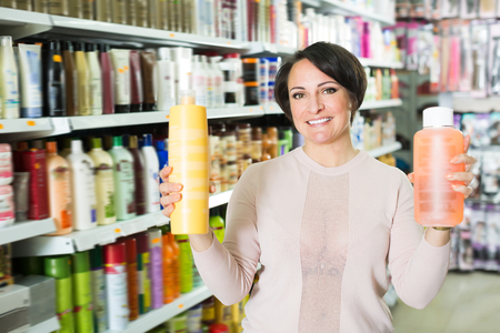 selecting: Happy woman selecting hair care products in shop and smiling Stock Photo