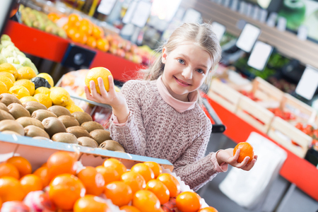 purchasers: Cute girl choosing sweet citrus fruits in supermarket