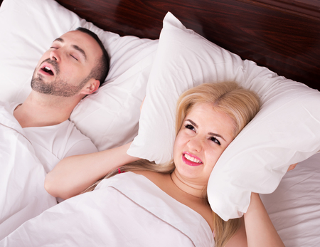 Upset young woman cannot sleep because of boyfriend snores loudly