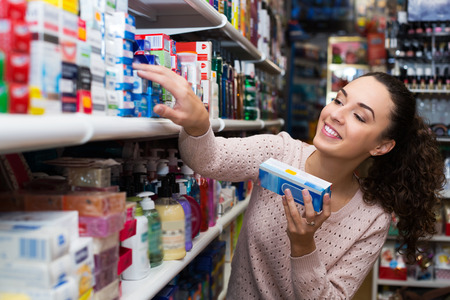 Positive customer buying toothpaste for sensitive teeth in store