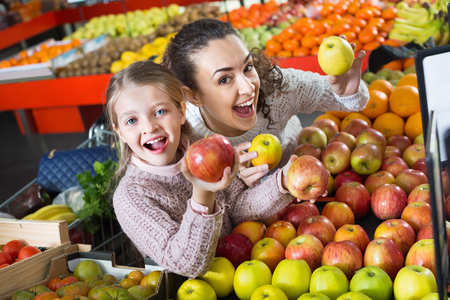 purchasers: Positive mother and  cute little daughter choosing seasonal fruits in grocery