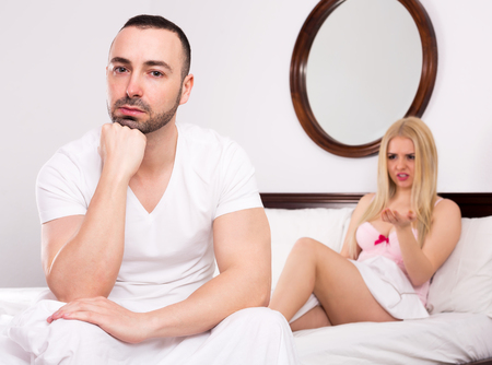 unsatisfied: Irritated girlfriend and sad man arguing in bedroom