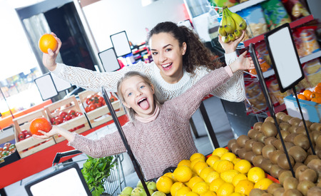 purchasers: Laughing mother and daughter buying fruits in supermarket