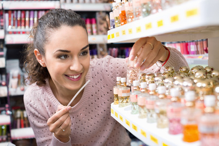 eau de perfume: Cheerful young  woman choosing fragrance on display and smiling