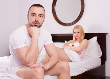 difficulties: Unsatisfied wife and sad young husband having difficulties in a bed
