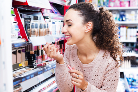 beauty shop: Portrait of young brunette selecting lip gloss at beauty shop