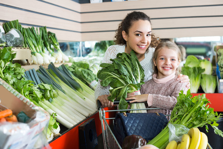 purchasers: Happy smiling mother with small daughter buying fresh celery and cabbage at market Stock Photo