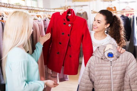 warm jacket: Pretty girlfriends choosing warm jacket in shopping center and smiling Stock Photo