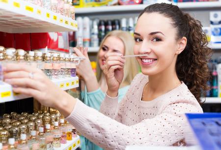 eau de perfume: Woman friends buying perfume in fragrance section of supermarket