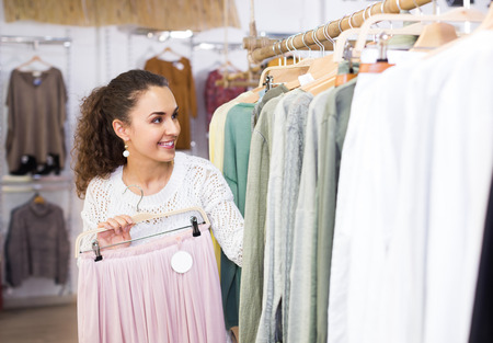 hobble: Cheerful young brunette woman buying new skirt at the store