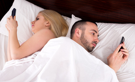 socialising: Young man and woman socialising with mobile phones in bed. Focus on the man