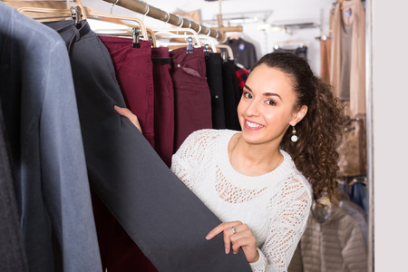 selecting: Smiling young female customer selecting new breeches at the store Stock Photo
