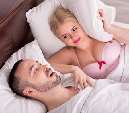 snoring: Unhappy blond wife disturbed with husband snoring in sleep in bedroom