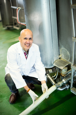 livestock sector: Mature employee working in raw milk sector of livestock farm Stock Photo