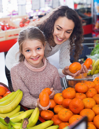 citrus family: Happy mother and small cheerful daughter buying sweet citrus fruits Stock Photo