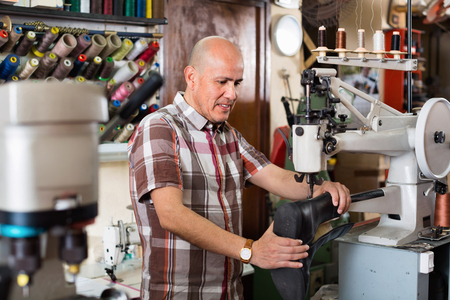 broaching: Mature efficient positive  workman sewing leather boots on stitch lathe in workshop