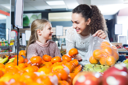 purchasers: Ordinary mother and daughter buying ripe fruits in supermarket