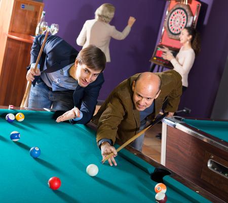clase media: Positivo clase media personas maduras y j�venes que tienen piscina juego en el club de billar