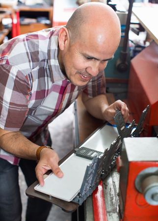 diligent: Diligent smiling senior man doing vehicle numbers on machine in workshop