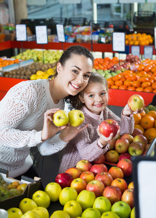 purchasers: Positive mother and  little daughter choosing seasonal fruits in grocery