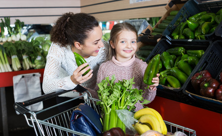 purchasers: Happy young mother with smiling little girl purchasing shallot and celery Stock Photo