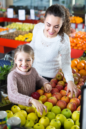 purchasers: Portrait of happy smiling mother and little daughter buying ripe apples at the market. Focus on girl