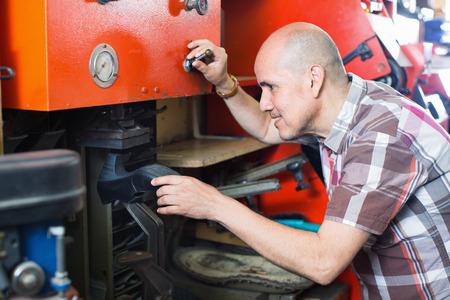 footwear: Professional skilled smiling  shoemaker heeling footwear on machine in workshop