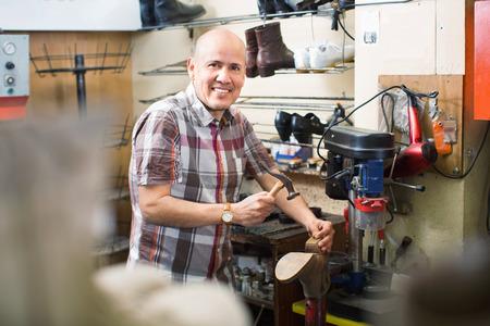 footwear: Professional diligent smiling shoemaker heeling footwear on machine in workshop