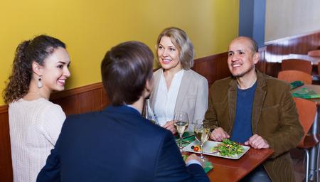 clase media: gente de clase media positivos disfrutando de la comida y el vino en el café Foto de archivo