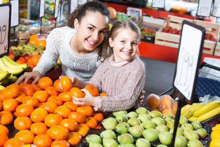 purchasers: Smiling young woman with cute little daughter choosing fruits at market Stock Photo