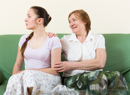 fracas: Mature mother and  adult daughter  after quarrel  in living room Stock Photo