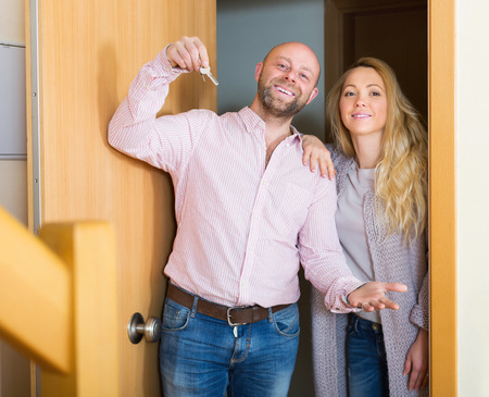 hypothec: Smiling husband and wife standing at entrance of new house
