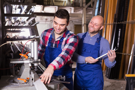 thermoplastic: Two happy men in uniform working on machine in PVC shop