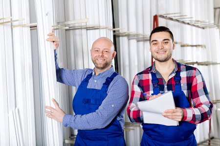 skilled operator: Happy young manager approving employee work at PVC windows factory Stock Photo