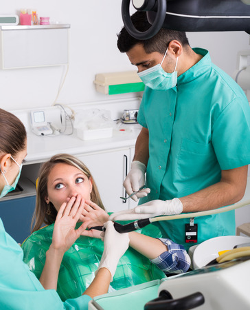 Portrait of dentist and frightened patient at dental clinic