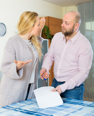 covetous: Unpleased couple having conflict over financial documents at home. Focus on woman Stock Photo