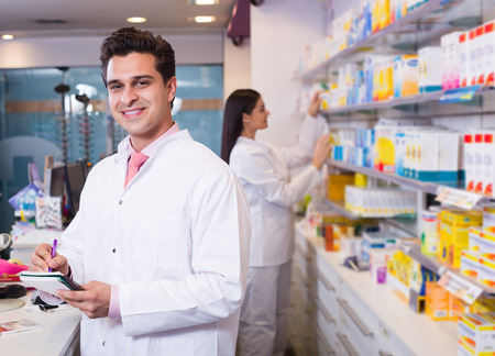 Professional pharmaceutists at reception of drugstore ready to help
