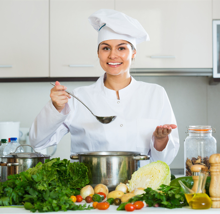 25s: Portrait of young smiling professional chef with vegetables and herbs