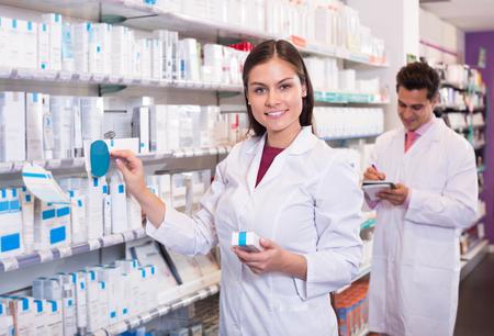 Equipo joven de pharmaceutist y técnico que trabaja en la tienda de farmacia