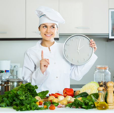 checking ingredients: Portrait of young professional chef with vegetables and clock Stock Photo