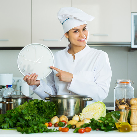 checking ingredients: Portrait of professional smiling positive chef with vegetables and clock