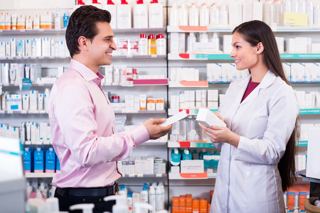 farmacy: Positive pharmacist counseling customer about drugs usage in modern farmacy