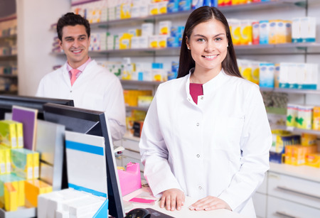 Retrato de farmacéutico alegre y un asistente que trabaja en la recepción farmacia