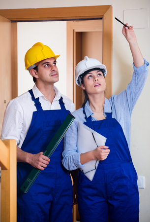 specialists: Professional maintenance crew of two smiling  american specialists in helmets indoors Stock Photo
