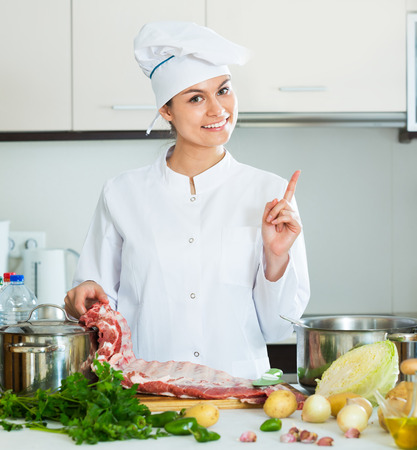 Professional happy chef with ribcage cooking at the kitchen table Stock Photo
