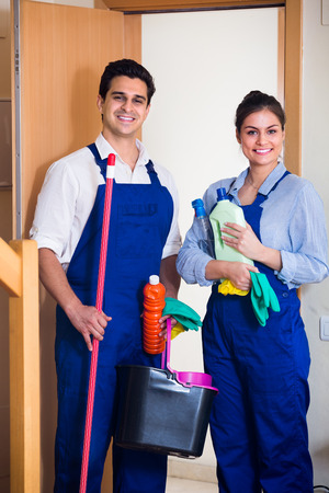 office cleanup: Portrait of people in overalls with supplies ready for cleaning indoor